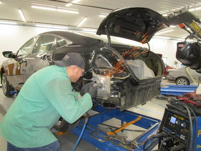 a technician working on a car at Bates Collision