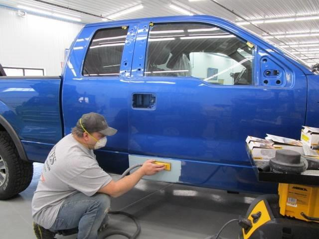 a technician repairing the side of a blue Ford truck at Bates Collision