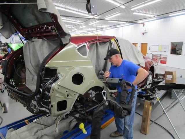 a technician at Bates Collision repairing the back of a car