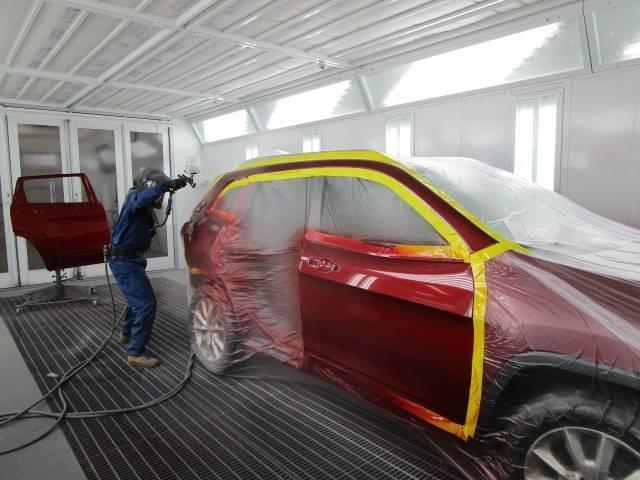 a Bates Collision team member painting a car red
