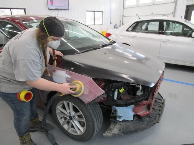 a Bates Collision technician buffing out the front of a car