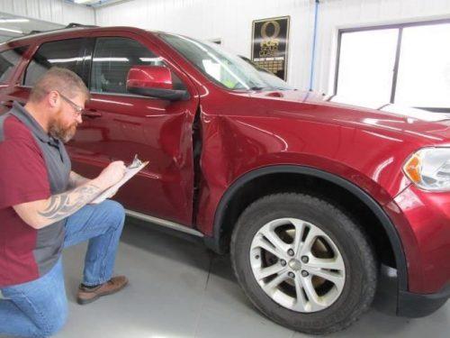 a technician examining a car dent at Bates Collision