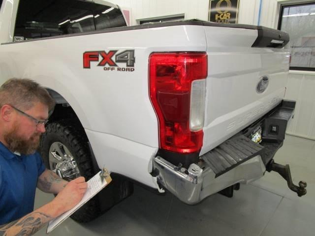 a technician working on a white Ford truck at Bates Collision